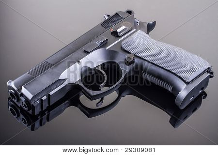 9 mm hand gun on glass table with reflection