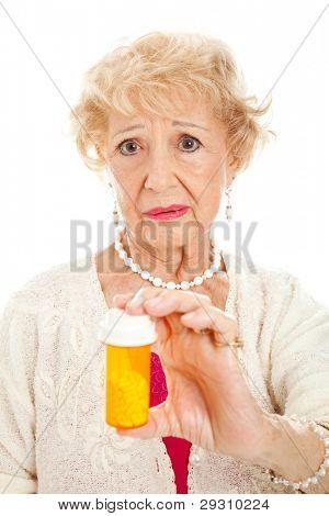 Sad senior woman holding a bottle of pills.  White background.