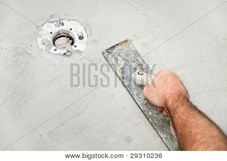 Using a float to smooth concrete during a bathroom remodel project.  Room for text.