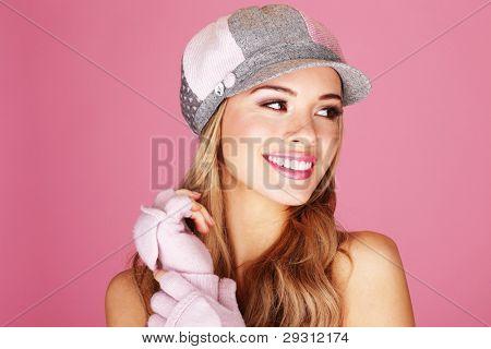 A pretty blonde woman giving a beautiful big smile wearing corduroy cap