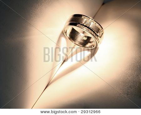 "Wedding Luxury Diamond ring casting a heart on Book Using for ""Love never ends"" Concept in Valentine Holiday"