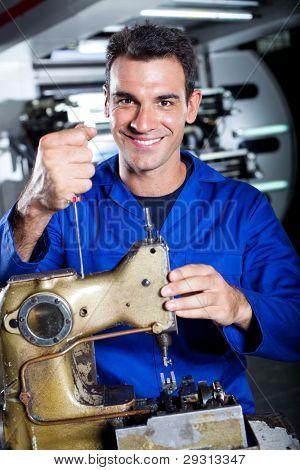 happy industrial mechanic repairing sewing machine