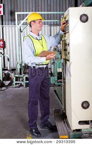 industrial machine operator setting up machine