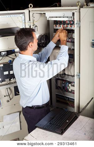 industrial engineer repairing computerized industrial machine