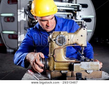 male technician fixing industrial sewing machine in factory
