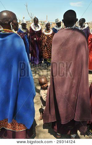 OLDUVAI GORGE, TANZANIA, MAASAI WOMEN IN A CIRCLE AND SMALL CHILD PEEKS BETWEEN THEM