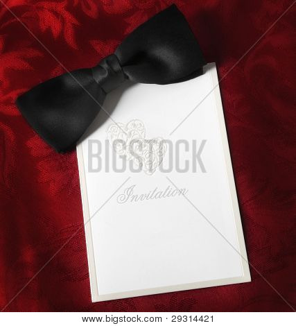Invitation, with black bow tie over rich red brocade background.