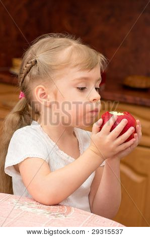 A child eats a juicy fresh apple.