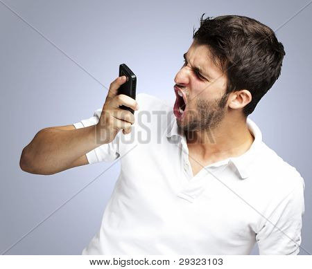 portrait of angry young man shouting using mobile over blue back