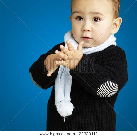 portrait of adorable kid clapping against a blue background