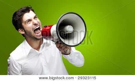 portrait of young man handsome shouting using megaphone over green background