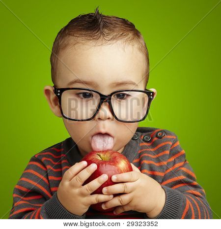 portrait of a handsome kid wearing glasses sucking a red apple over green