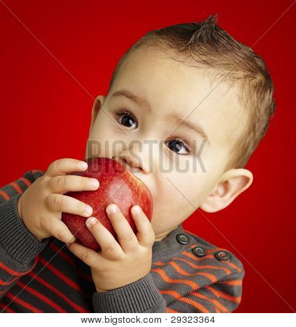 portrait of a handsome kid sucking a red apple over red background