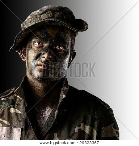 portrait of young soldier face with jungle camouflage over black and white background