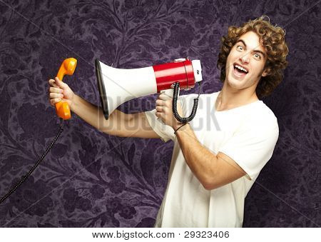 portrait of young man shouting with megaphone and talking on vintage telephone against a vintage wall