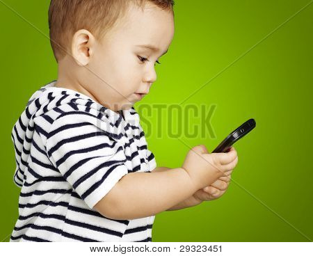 portrait of funny kid touching mobile over green background