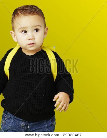 portrait of adorable kid carrying yellow backpack over yellow background