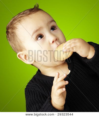 portrait of kid eating a biscuit over green background