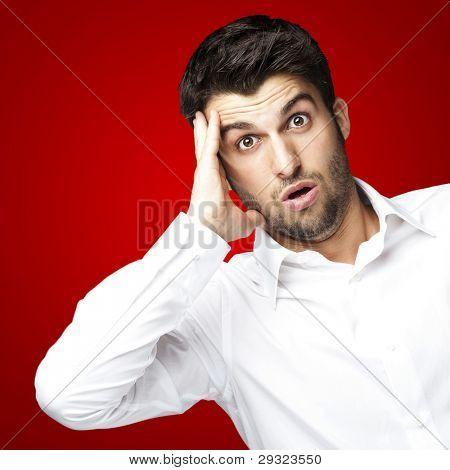 Portrait of young Man vor einem roten Hintergrund überrascht