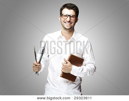 portrait of a handsome young student holding paintbrushes over grey background