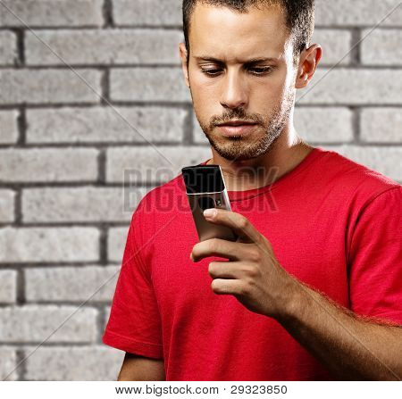 young man typing on mobile phone against a bricks wall