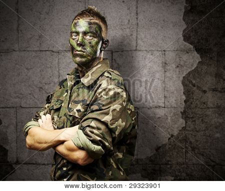 portrait of young soldier with jungle camouflage paint against a grunge bricks background