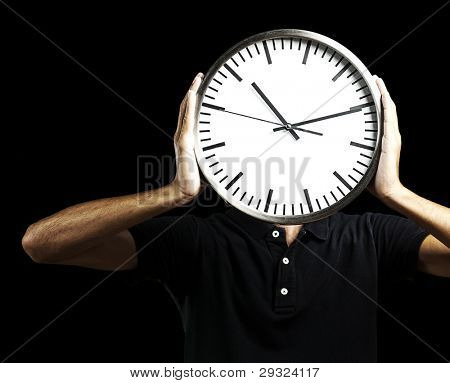 young man holding big clock covering his face over black background