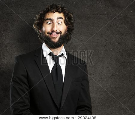 portrait of young business man showing the tongue against a grunge wall