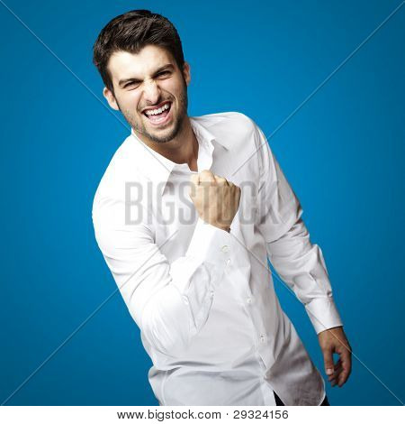 portrait of young man winner gesture against a blue background