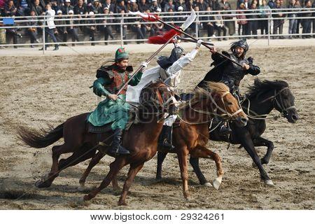 WUXI, CHINA - 25 de novembro: Cavaleiros cavalo luta fora uma antiga guerra em um teatro ao ar livre em nenhuma