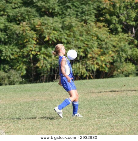 Youth Girl Bouncing Soccer Ball Off Chest