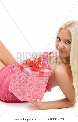 Beautiful sexy blonde woman in pink dress with red present box in hands over white background