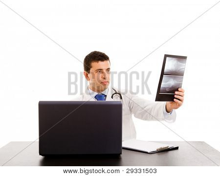 Closeup of doctor at his desk in front of computer analyzing an x-ray