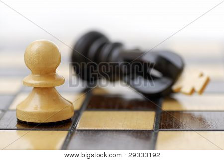 White Pawn Standing Over Defeated King.