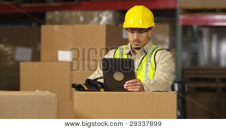 Worker in warehouse using digital tablet