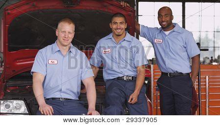 Retrato de tres mecánicos de tienda de auto