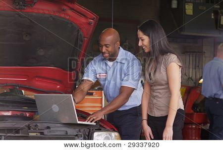 Auto Shop Mechanic working on Laptopcomputer mit Kunden