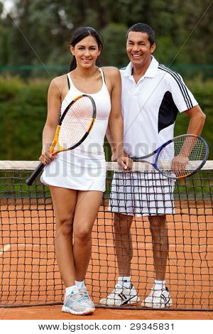 Couple at the court playing tennis and holding rackets