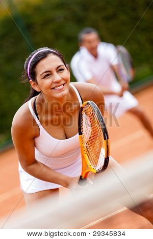 Couple playing doubles at the tennis court