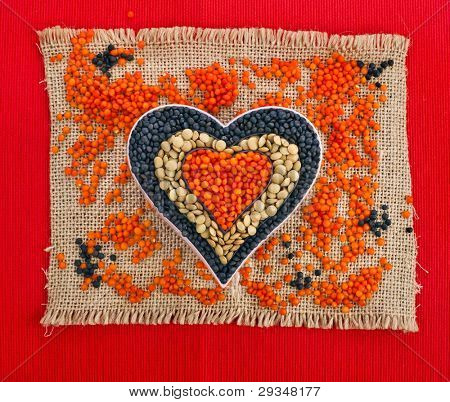 different types of grains of lentils in the form of heart on red canvas  background