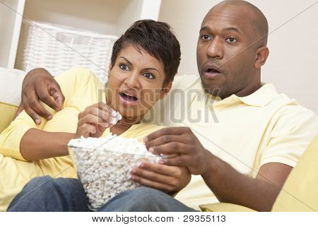 A happy African American man and woman couple in their thirties sitting at home, eating popcorn and looking shocked watching a movie or television