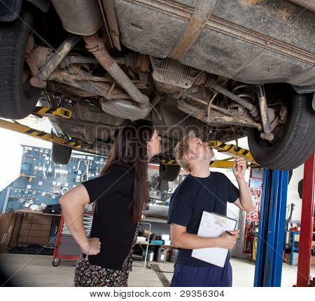 A young mechanic showing a female customer what was done to her car