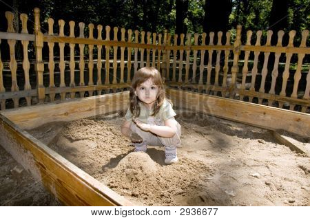 Child Girl Plaing At Wood Sand-Box In Summer Park