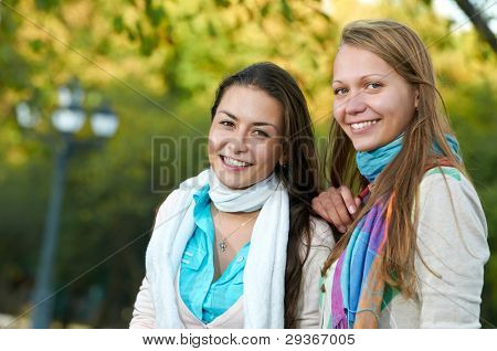 portrait of Two young smiling cheerful girl students outdoors in autumn