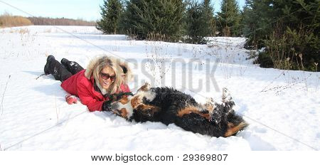 Woman Petting Her Dog In Snow