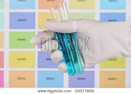 Two tubes with blue and dark blue liquid in hand on color samples background