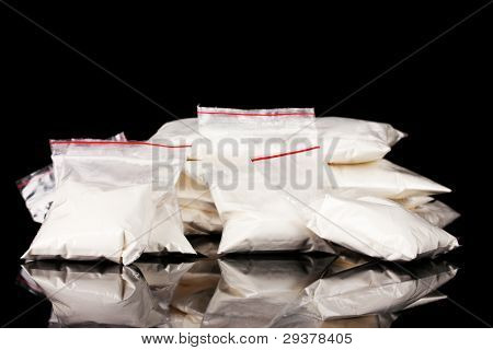 Cocaine in packages on black background