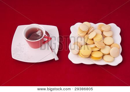 Cup Of Tea And Plate Of Mixed Macaroons On A Velvet Tablecloth