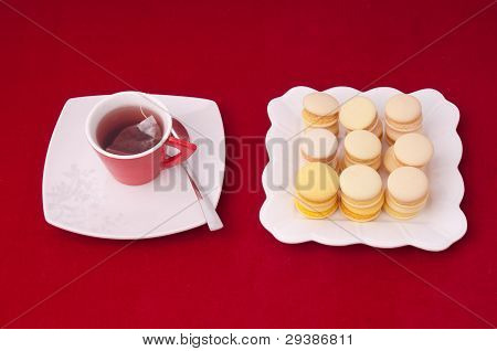 Cup Of Tea And Stacked And Aligned Macaroons On A Velvet Tableclothe.