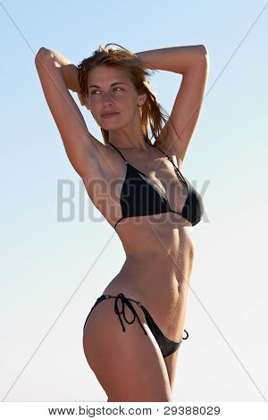 Young Woman In Bikini Posing At Sky Background